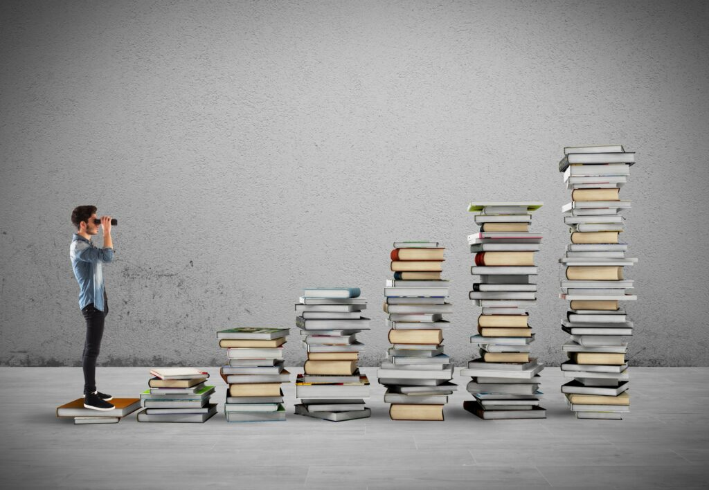 Man looking at stack of books